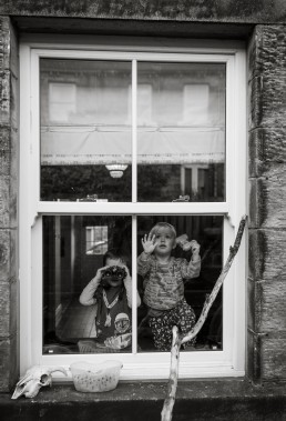Two young boys bird watching through house window. Black and white Photo