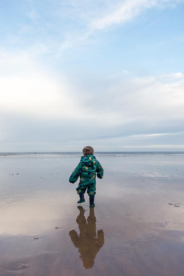 Toddler walking on sandy beach